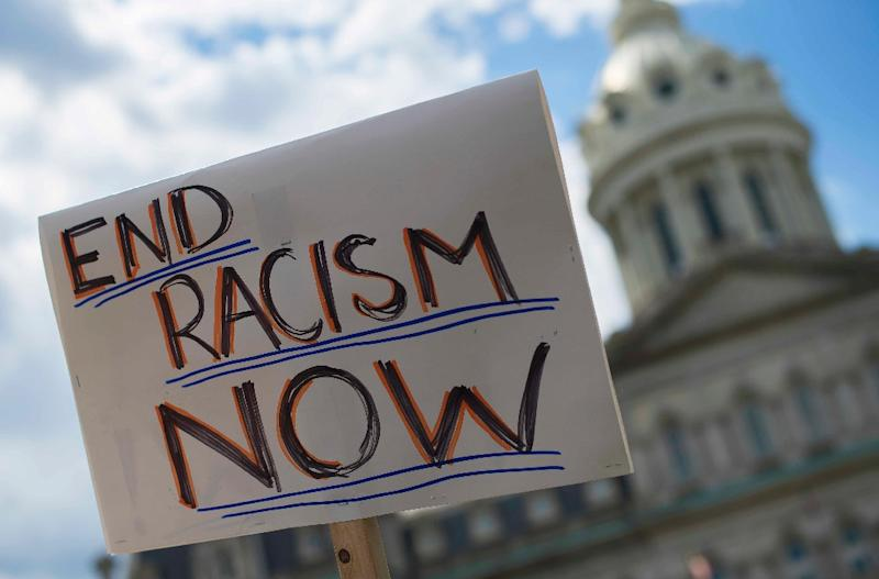 A protester holds up a placard during a rally outside City Hall in Baltimore, Maryland, on May 2, 2015 (AFP Photo/Jim Watson)
