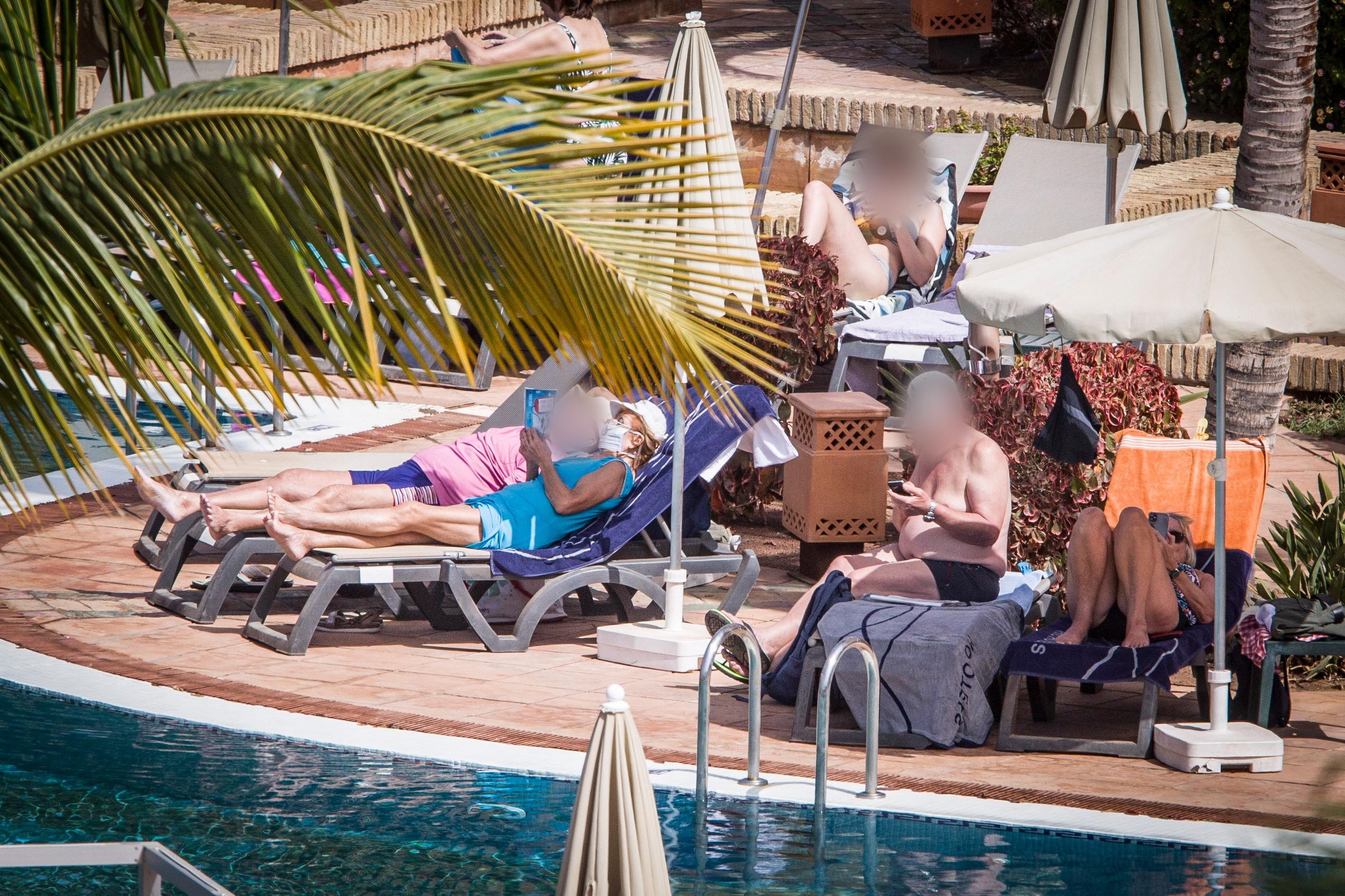 26 February 2020, Spain, Teneriffa: Hotel guests sunbathe by the pool. The hotel in Tenerife, which has been quarantined because of coronavirus cases, continues to be cordoned off by the police. Photo: Arturo Rodríguez/dpa - only for use in accordance with contractual agreement (Photo by Arturo Rodríguez/picture alliance via Getty Images)