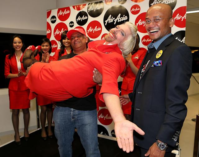 PERTH, AUSTRALIA - MAY 12: Sir Richard Branson is held in the arms of Tony Fernandes prior to their flight to Kuala Lumpur at Perth International Airport on May 12, 2013 in Perth, Australia. Sir Richard Branson lost a friendly bet to AirAsia Group Chief Executive Officer Tony Fernandez after wagering on which of their Formula One racing teams would finish ahead of each other in their debut season of the 2010 Formula One Grand Prix in Abu Dhabi and that the loser would serve as a female flight attendant on board the winner's airline. (Photo by Paul Kane/Getty Images)