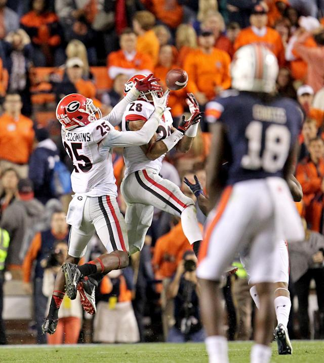Georgia free safety Tray Matthews (28) and strong safety Josh Harvey-Clemons (25) try to intercept as pass late in the fourth quarter of an NCAA college football game against Auburn at Jordan-Hare Stadium on Saturday, Nov. 16, 2013 in Auburn. Ala. Auburn wide receiver Ricardo Louis, hidden, came up with the catch and ran for the game-winning touchdown. Auburn won 43-38.(AP Photo/Atlanta Journal-Constitution, Jason Getz)