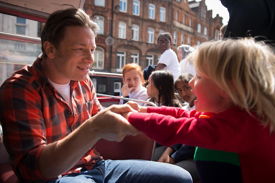 British Chef and television presenter Jamie Oliver plays with his son Buddy during an open-top bus tour of London to promote Food Revolution Day on May 15, 2015. Jamie Oliver is calling for a global campaign to put compulsory practical food eduction on the school curriculum of the G20 countries. AFP PHOTO / LEON NEAL        (Photo credit should read LEON NEAL/AFP/Getty Images)