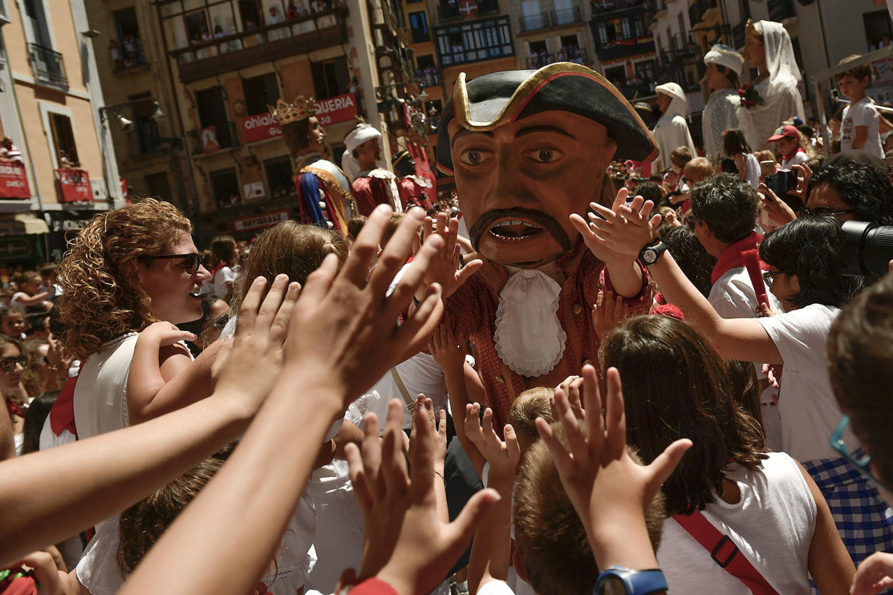<p>Revellers gather around of one member of The 'Comparsa de Gigantes y Cabezudos' or the Parade of the Giants and Big Headsarade, on the last day at the San Fermin Festival, in Pamplona, northern Spain, July 14, 2017. (Photo: Alvaro Barrientos/AP) </p>