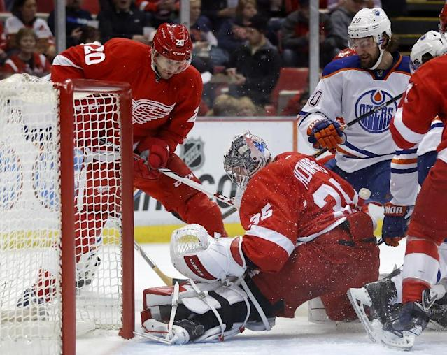 Detroit Red Wings goalie Jimmy Howard (35) stops a shot during a scrum at the net against Edmonton Oilers' Luke Gazdic, right, as Detroit Red Wings' Drew Miller, left, helps defend during the first period of an NHL hockey game Friday, March 14, 2014, in Detroit. (AP Photo/Duane Burleson)