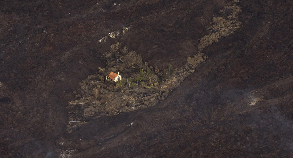 A photo of a house surrounded by land that has been charred by lava.