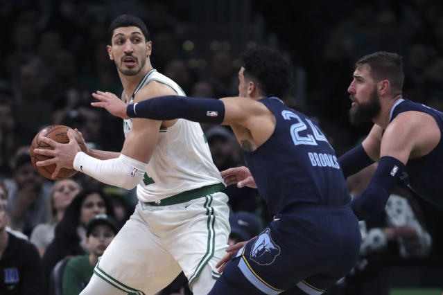 Boston Celtics center Enes Kanter, left, looks to pass while covered by Memphis Grizzlies guard Dillon Brooks (24) and center Jonas Valanciunas, right, during the first half of an NBA basketball game in Boston, Wednesday, Jan. 22, 2020. (AP Photo/Charles Krupa)