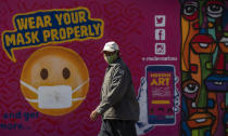 A man walks past a mural on how to wear a face mask to prevent the spread of coronavirus, in Soweto, South Africa, Saturday, May 15, 2021. (AP Photo/Themba Hadebe)