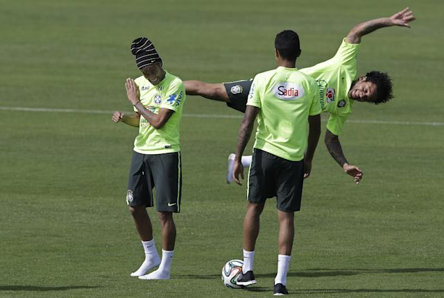 Brazil's Mrcelo, behind right, jokes with teammate Neymar, left, during a training session at the Granja Comary training center in Teresopolis, Brazil, Saturday, June 14, 2014. Brazil plays in group A at the 2014 soccer World Cup. (AP Photo/Andre Penner)