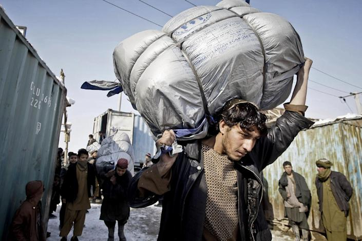 Internally displaced Afghans from Helmand province, carry sacks of blankets to be donated by the United Nation's refugee agency (UNHCR) at a refugee camp in Kabul, Afghanistan, Sunday, Dec. 30, 2012. Around 600 internally displaced families received winter relief assistance distributed by the United Nation's refugee agency. (AP Photo/Musadeq Sadeq)