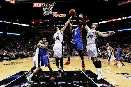 May 21, 2014; San Antonio, TX, USA; Oklahoma City Thunder guard Russell Westbrook (0) drives to the basket as San Antonio Spurs guard Danny Green (4) and forward Tiago Splitter (22) defend in game two of the Western Conference Finals of the 2014 NBA Playoffs at AT&T Center. Soobum Im-USA TODAY Sports