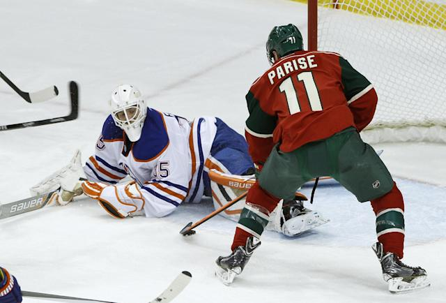 Minnesota Wild left wing Zach Parise (11) scores on Edmonton Oilers goalie Viktor Fasth, left, of Sweden, during the first period of an NHL hockey game in St. Paul, Minn., Tuesday, March 11, 2014. (AP Photo/Ann Heisenfelt)