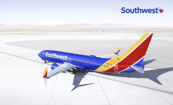 An aircraft painted blue, yellow, and red, sitting on a runway, with the Southwest corporate logo on the side.