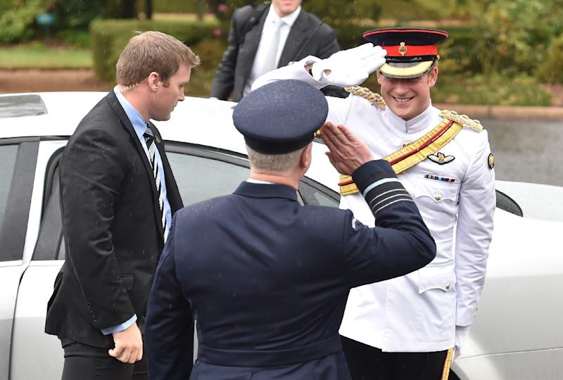 Britain's Prince Harry (R) and Australian Defence Force chief Air Chief Marshal Mark Binskin salute each other after arriving at the Royal Military College, Duntroon, in Canberra, on April 6, 2015 (AFP Photo/Peter Parks)