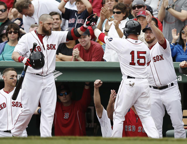 Boston Red Sox's Dustin Pedroia (15) is congratulated by teammates Jonny Gomes, left, and starting pitcher Ryan Dempster, right, after scoring on a hit by David Ortiz during the third inning of a baseball game against the New York Yankees at Fenway Park in Boston Saturday, Sept. 14, 2013. (AP Photo/Winslow Townson)