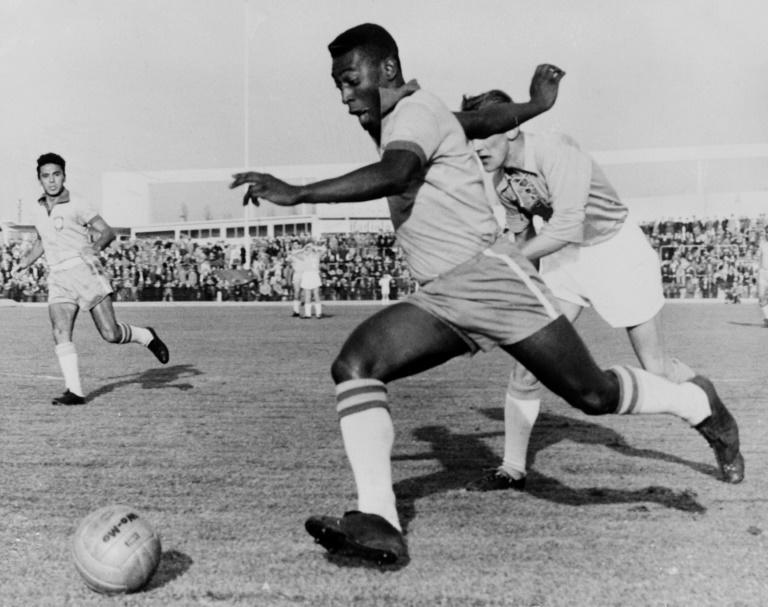 In this photo taken on May 8, 1960, Brazilian football legend Pele dribbles past a defender during a friendly match between Malmoe and Brazil, in Sweden
