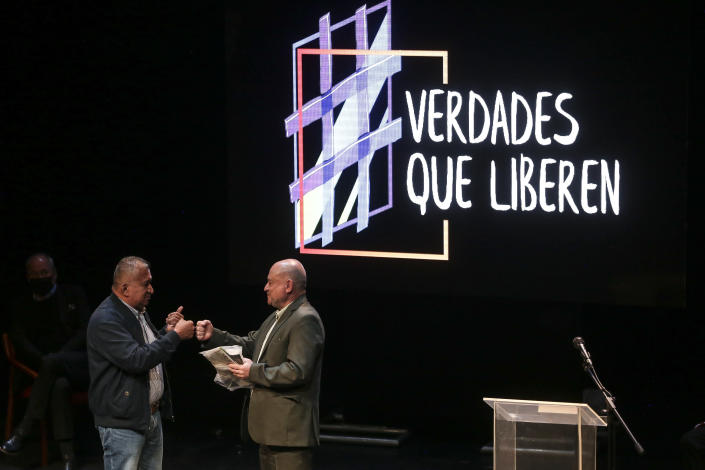 Armando Acuña, left, a former city councilman who was kidnapped by the Revolutionary Armed Forces of Colombia, FARC, hands former FARC commander Carlos Antonio Lozada, the bag Acuña was given by the rebels for his personal belongings while he was in captivity, during an event at the Truth Commission to commemorate victims of the country's decades-long armed conflict, in Bogota, Colombia, Wednesday, June 23, 2021. (AP Photo/Ivan Valencia)