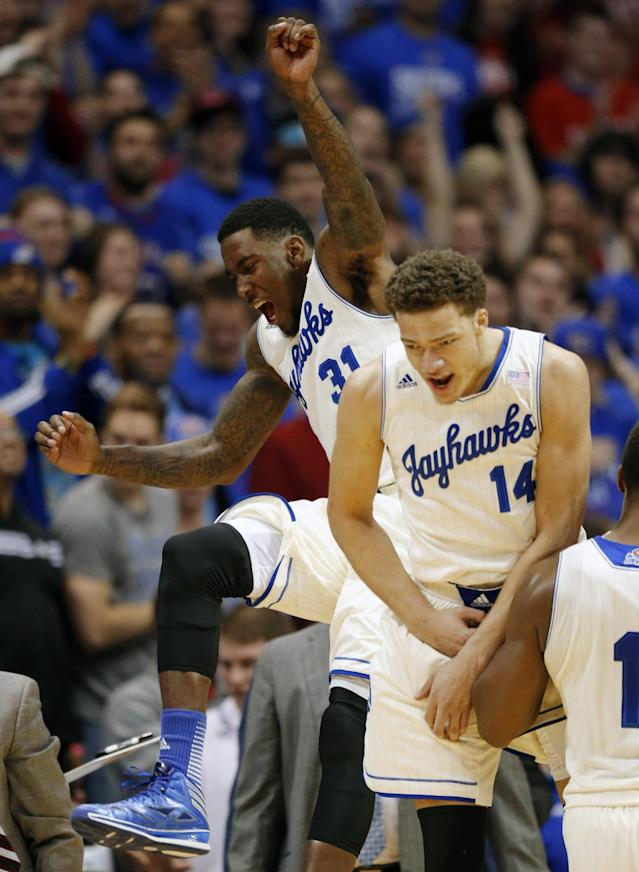 Kansas forward Jamari Traylor (31) and guard Brannen Greene (14) celebrate at a timeout during the first half of an NCAA college basketball game against Oklahoma State at Allen Fieldhouse in Lawrence, Kan., Saturday, Jan. 18, 2014. (AP Photo/Orlin Wagner)