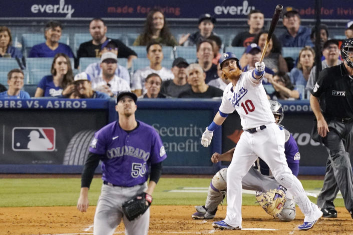 Los Angeles Dodgers' Justin Turner, right, heads to first as he hits a solo home run as Colorado Rockies starting pitcher Chi Chi Gonzalez watches during the third inning of a baseball game Friday, July 23, 2021, in Los Angeles. (AP Photo/Mark J. Terrill)