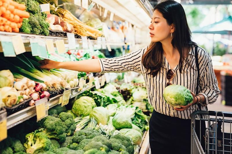 asian local woman buy vegetables and fruits in supermarket touches them demonstrating need to disinfect amid coronavirus pandemic