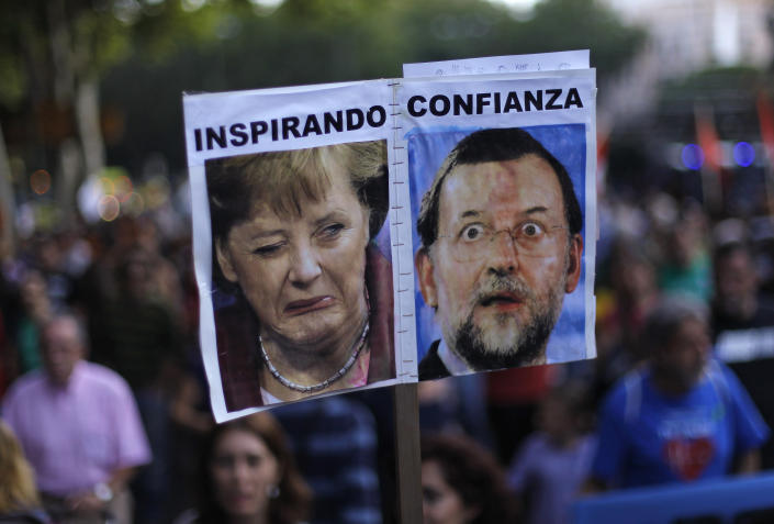 """Protestors hold a banner with a photo of German Prime Minister Angela Merkel and Spanish Prime Minister Mariano Rajoy reading """"inspiring confidence"""" as they march against healthcare austerity measures announced by the Spanish government in Madrid, Spain, Saturday, Oct. 6, 2012. Hundreds of Spaniards concerned with government cuts to healthcare and civil servants hit with another freeze on their wages for next year hold a protest in downtown Madrid. (AP Photo/Andres Kudacki)"""