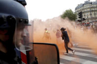 Protestors move away from gas canisters during a demonstration in Paris, France, Saturday, July 31, 2021. Demonstrators gathered in several cities in France on Saturday to protest against the COVID-19 pass, which grants vaccinated individuals greater ease of access to venues. (AP Photo/Adrienne Surprenant)