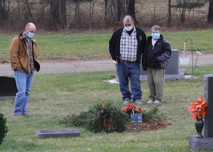 "Frank ""Keith"" Malinowski, left, visits the grave of his sister, Jamie Malinowski, with parents Frank and Jody Malinowski in Doylestown, Ohio."