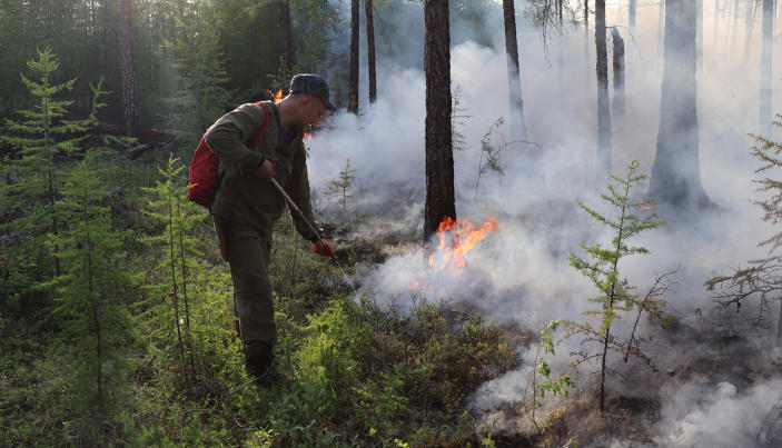 FILE - In this file photo provided by Russian Emergency Ministry Press Service, a firefighter douses a forest fire in Yakutia region, Russia, Wednesday, July 14, 2021. Each year, thousands of wildfires engulf wide swathes of Russia, destroying forests and shrouding broad territories in acrid smoke. This summer has seen particularly massive fires in Yakutia in northeastern Siberia following unprecedented heat. (Russian Emergency Ministry Press Service via AP, File)