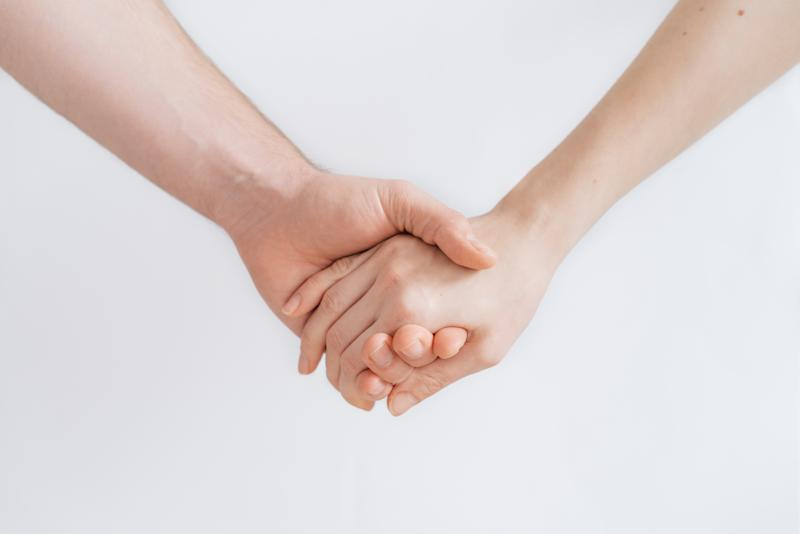 Cropped Image Of Couple Holding Hands Against White Background
