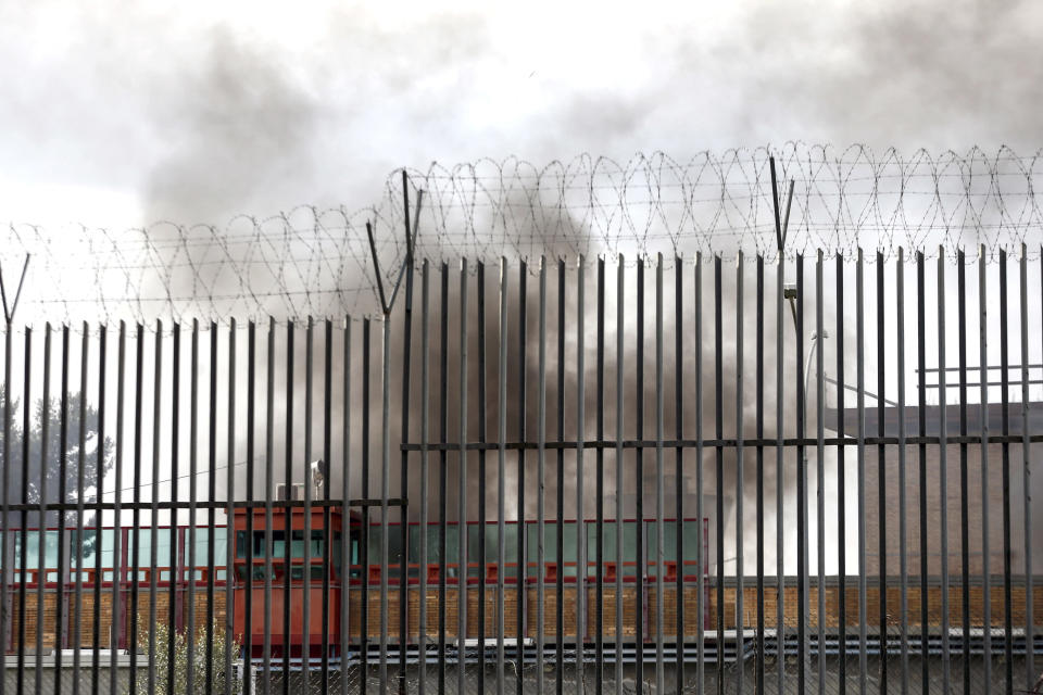 Smoke billows from Rebibbia prison following inmates' protests, in Rome, Monday, March 9, 2020. Italian penitentiary police say six inmates protesting coronavirus containment measures at the northern Italian prison of Modena have died after they broke into the infirmary and overdosed on methadone. The protest Sunday in Modena was among the first of more than two-dozen riots at Italy's overcrowded lock-ups that grew Monday. (Cecilia Fabiano/LaPresse via AP)