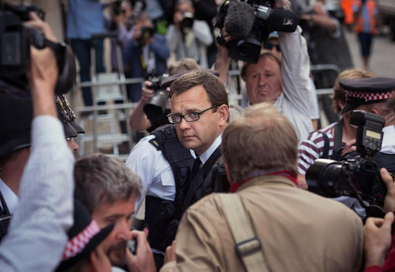 Former News of the World editor Andy Coulson, centre, arrives at the Old Bailey court to receive his sentence, in London, Friday, July 4, 2014. Coulson, 46, has been found guilty of being involved in the conspiracy to hack into the phone voicemails of many celebrities, royals, politicians and ordinary members of the public, at the now-closed British Sunday tabloid newspaper. Coulson has been sentenced to 18 months in jail. (AP Photo/PA, Stefan Rousseau) UNITED KINGDOM OUT