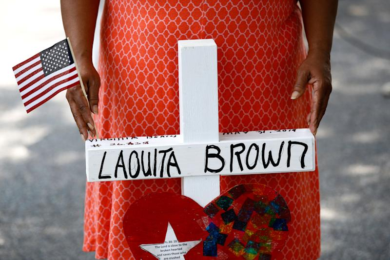 Patricia Olds rests her hands on a cross bearing the name of Olds' coworker, LaQuita Brown, a victim of a mass shooting at a municipal building in Virginia Beach, Va., before carrying the cross to a nearby makeshift memorial, June 2, 2019. (Photo: Patrick Semansky/AP)