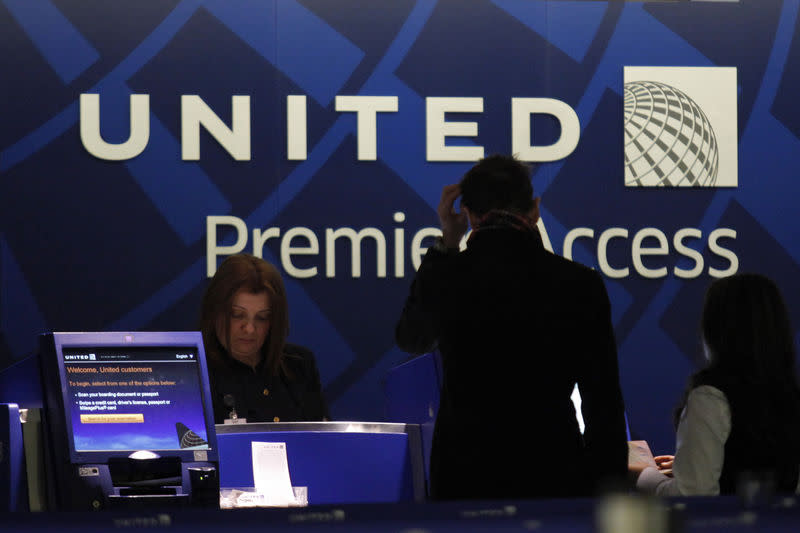 FILE PHOTO: A worker from United attends to some customers during their check in process at Newark International airport in New Jersey