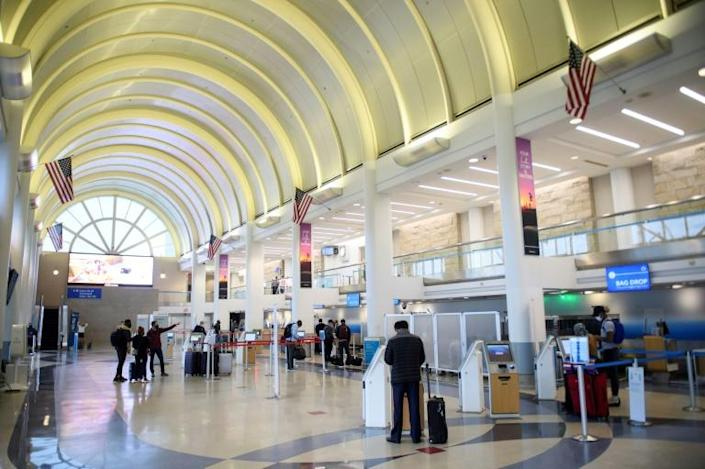 Passengers check in at Los Angeles International Airport ahead of Thanksgiving in Los Angeles, California, November 25, 2020, after US health authorities urged Americans not to travel for the annual holiday