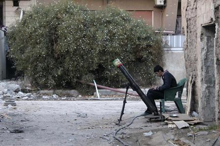 A Free Syrian Army fighter listens to music as he sits beside a rocket launcher in Damascus