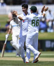 Pakistan bowler Naseem Shah, left, celebrates the wicket of Henry Nicholls during play on day two of the first cricket test between Pakistan and New Zealand at Bay Oval, Mount Maunganui, New Zealand, Sunday, Dec. 27, 2020. (Andrew Cornaga/Photosport via AP)