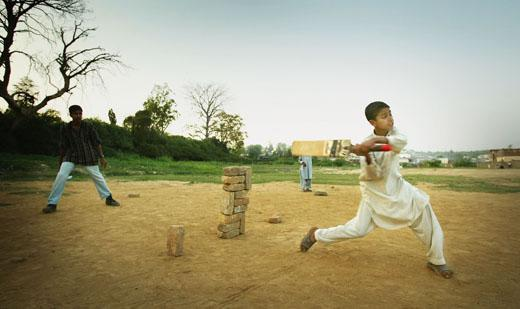 RAWALPINDI, PAKISTAN - MARCH 21:  Children play a game of cricket on March 21, 2004 in Rawalpindi, Pakistan. Cricket fever has gripped Pakistan as the Indian team play their first full tour of Pakistan in almost 15 years, comprising five one-day internationals followed by three Tests. The tour is seen as evidence that the two nuclear-armed rivals are getting closer after almost going to war over the Himalayan region of Kashmir less than two years ago. (Photo by Scott Barbour/Getty Images)   *** Local Caption ***
