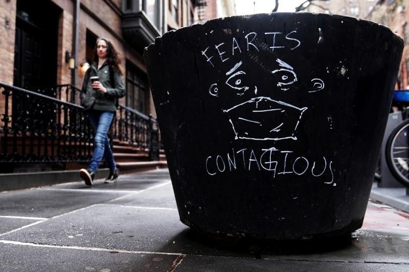 "FILE PHOTO: ""Fear is contagious"" graffiti is pictured on a pot outside an NYU dormitory following the outbreak of coronavirus disease (COVID-19), in the Manhattan borough of New York City"