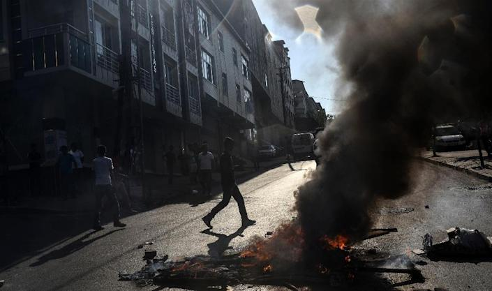 Protesters disperse around a street fire during clashes with Turkish police officers on July 26, 2015 in the Gazi district of Istanbul (AFP Photo/Bulent Kilic)