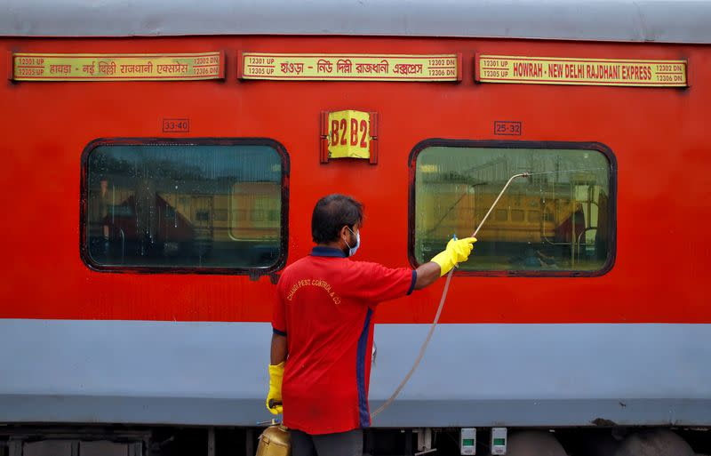 A worker disinfects the exteriors of a passenger train parked at a railway yard as a preventive measure against coronavirus, on the outskirts of Kolkata