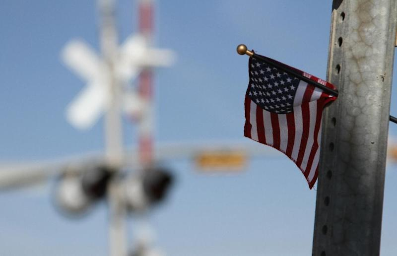 A flag is left at the scene of an accident where four veterans were killed and 16 other people were injured when a train slammed into a parade float carrying the returning heroes to a banquet last Thursday in Midland, Texas on Saturday, Nov. 17, 2012.   Federal investigators were trying to determine whether the two-float parade had been given enough warning to clear the tracks.  (AP Photo/Juan Carlos Llorca)