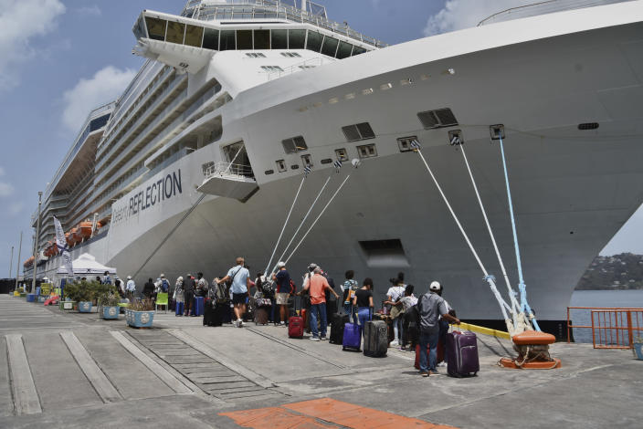 British, Canadian, and U.S. nationals line up alongside the Royal Caribbean cruise ship Reflection to be evacuated free of charge, in Kingstown on the eastern Caribbean island of St. Vincent, Friday, April 16, 2021. La Soufriere volcano has shot out another explosive burst of gas and ash Friday morning as the cruise ship arrived to evacuate some of the foreigners who had been stuck on a St. Vincent island by a week of violent eruptions. (AP Photo/Orvil Samuel)