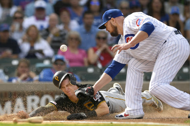 Pittsburgh Pirates' Kevin Newman left, slides safely into home plate on a throwing error by Chicago Cubs center fielder Albert Almora Jr. as Chicago Cubs starting pitcher Jon Lester right, tries to apply the tag during the first inning of a baseball game Friday, Sept. 13, 2019, in Chicago. (AP Photo/Paul Beaty)