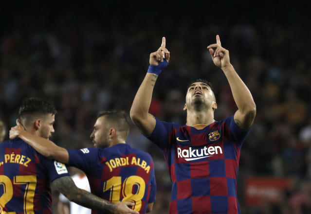 Barcelona's Luis Suarez, right, celebrates after scoring his side's fourth goal during the Spanish La Liga soccer match between FC Barcelona and Valencia CF at the Camp Nou stadium in Barcelona, Spain, Saturday, Sep. 14, 2019. (AP Photo/Joan Monfort)