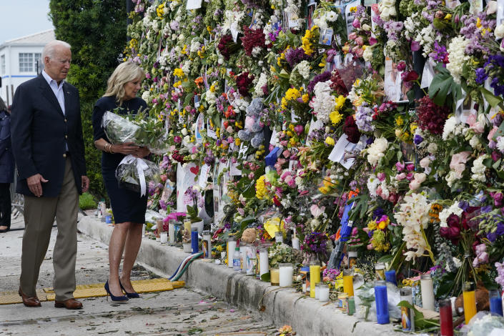 President Joe Biden and first lady Jill Biden visit memorial wall covered in flowers and photos of the missing after the Florida condo collapse Thursday, July 1, 2021, in Surfside, Fla. (AP Photo/Susan Walsh)