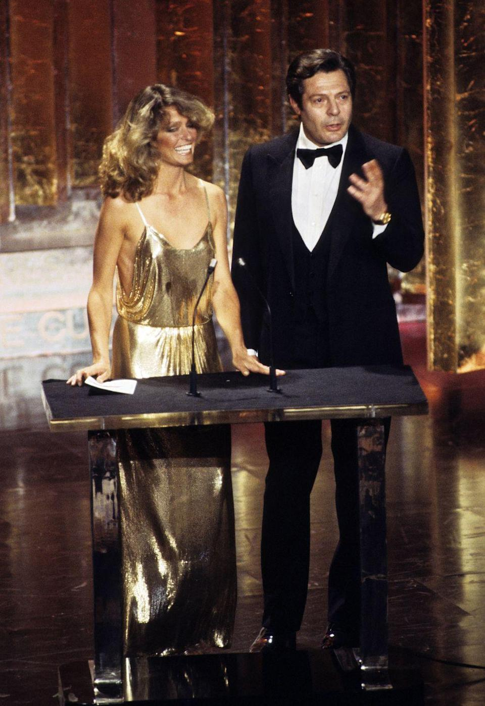 <p>Farrah Fawcett wore a metallic gold Halston dress to the 50th Annual Academy Awards. The <em>Charlie's Angels</em> actress is shown here with Italian actor Marcello Mastroianni.</p>