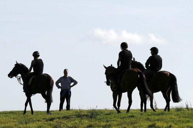Racehorse trainer George Baker talks with riders on the gallops near his Robins Farm stables