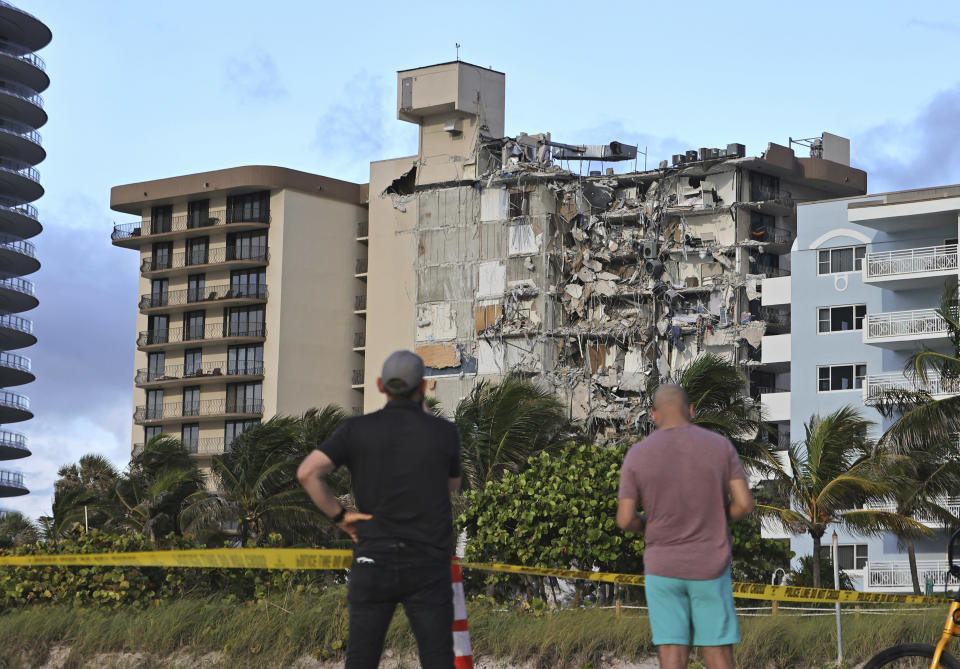People look at the partially collapsed Champlain Towers South Condo in Surfside, Fla., Thursday, June 24, 2021. (David Santiago/Miami Herald via AP)