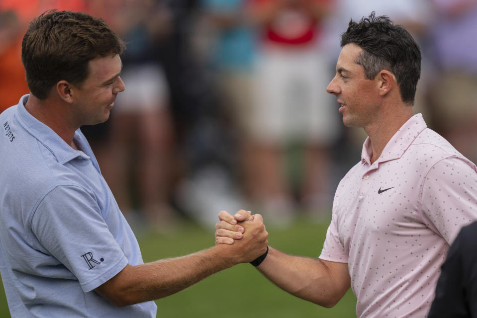 Keith Mitchell, left, congratulates Rory McIlroy on his win in the Wells Fargo Championship golf tournament at Quail Hollow on Sunday, May 9, 2021, in Charlotte, N.C. (AP Photo/Jacob Kupferman)