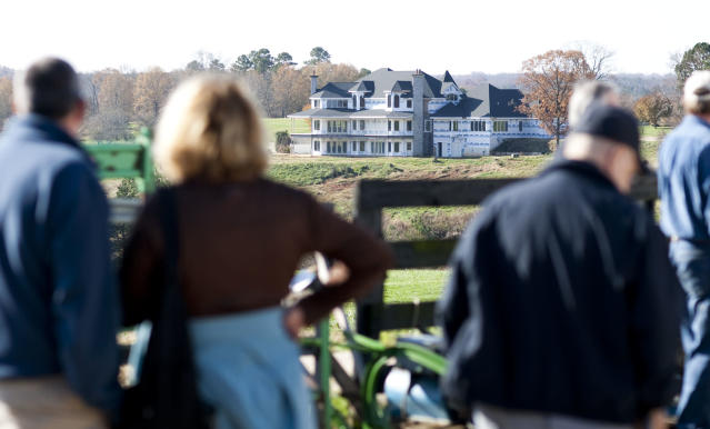 FILE - In this Nov. 20, 2009 file photo, auction attendees look at suspended NASCAR Sprint Cup driver Jeremy Mayfield's home, under renovation, during a public auction at Mayfield's Catawba, N.C. property. The million-dollar North Carolina home once owned by Mayfield before he was kicked off the land is scheduled to be burned to the ground as part of a fire training exercise. The Catawba County Fire Marshal's Office says the 12,000-square-foot unfinished house will be burned down on Saturday, Dec. 14, 2013. (AP Photo/Jason E. Miczek, File)