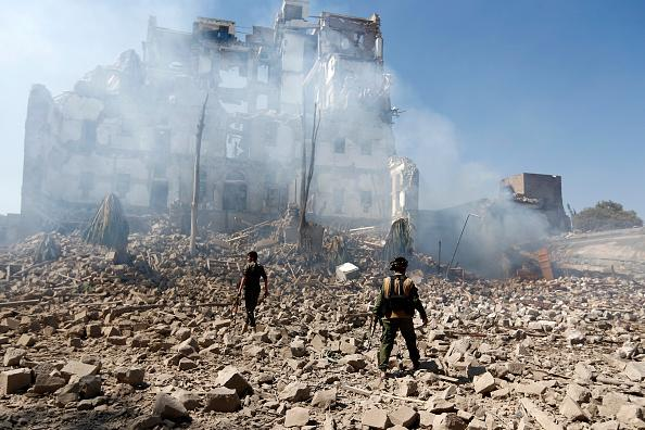 Huthi rebel fighters inspect the damage after a reported air strike carried out by the Saudi-led coalition targeted the presidential palace in the Yemeni capital Sanaa in December 2017. Source: Getty