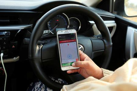 "Yasmin Perveen, one of the pioneer women ""captains"" of Careem, checks her work app before driving her car in Islamabad"
